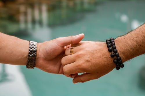 Crop anonymous homosexual male couple wearing wedding rings holding hands gently in blurred nature