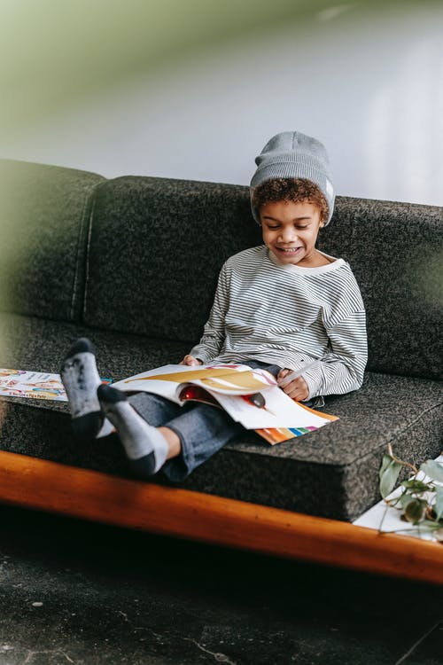 Full body of cheerful cute African American boy smiling and reading fascinating magazine on gray sofa of lounge