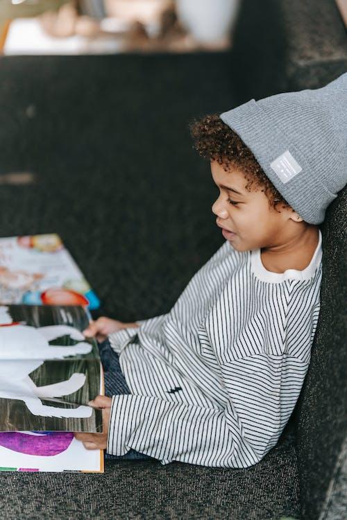 Cute black boy reading fairytale in book