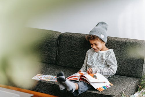 Full body of happy little African American boy smiling and watching pictures of fairytale in book