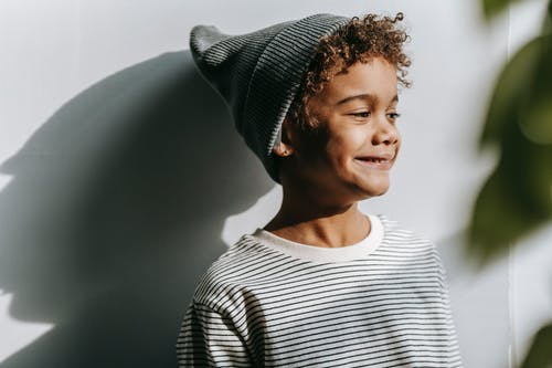 Cheerful African American boy in gray hat looking away and smiling near wall in daytime