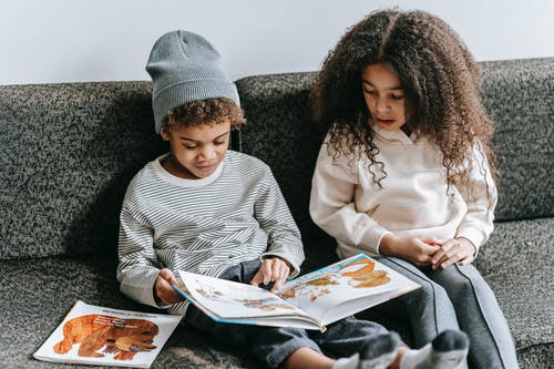 Focused black boy and girl watching interesting book