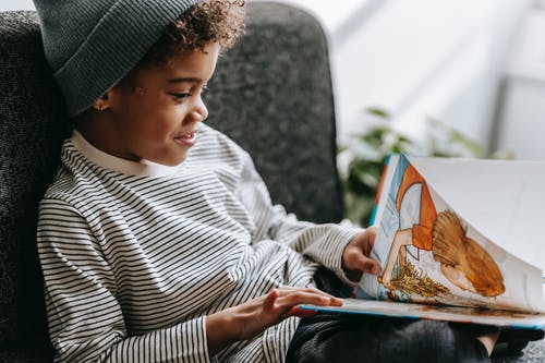 Side view of crop glad African American boy with curly hair smiling and watching pictures of book on blurred background