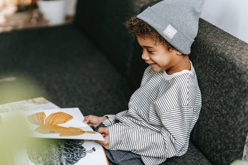 Cute glad black boy enjoying bright pictures in book