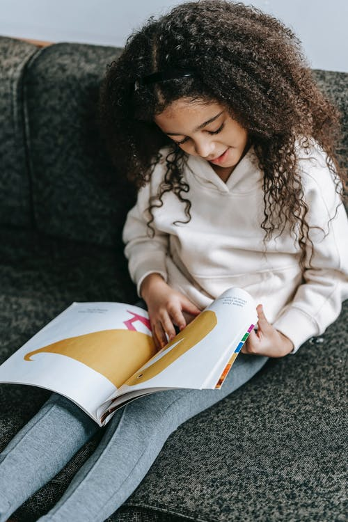 Cute cheerful African American girl with curly hair watching at bright illustrations of book on sofa