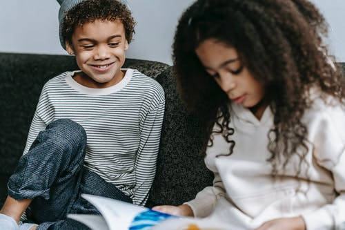 Black children studying and reading book together