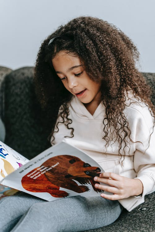 Adorable smart black girl reading book with animals