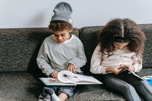 Little clever black friends studying books on sofa
