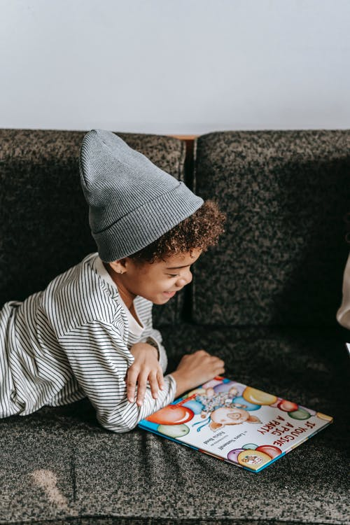 Side view of cheerful African American boy looking at illustration of book with fascinating fairytale