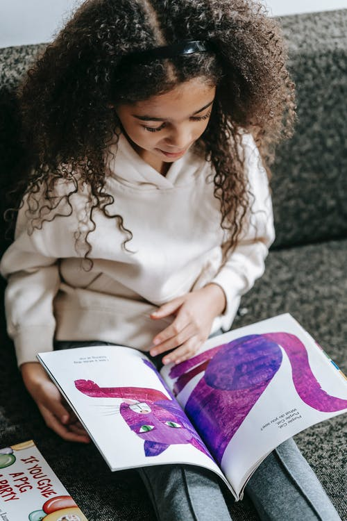 From above of crop African American cute smart girl reading book with bright illustration of cat