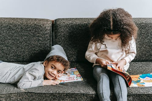 Happy black siblings resting on sofa with books