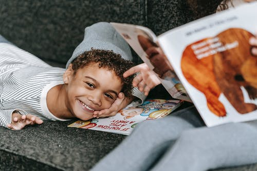 Cheerful little African American boy lying on comfortable sofa near friend reading book