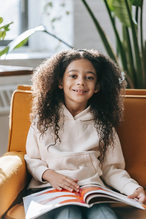 Happy African American girl in casual clothes reading interesting book and looking at camera with smile while sitting on comfortable armchair in light apartment