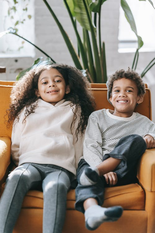 Cheerful stylish African American siblings sitting together on comfy armchair in light living room and looking at camera with toothy smiles