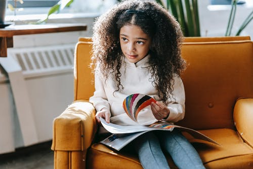Sweet black girl reading book on cozy armchair