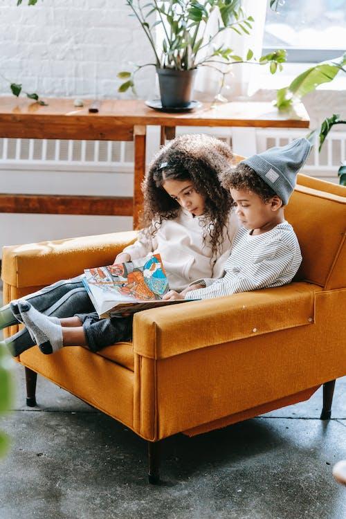 Pensive black kids reading book on armchair