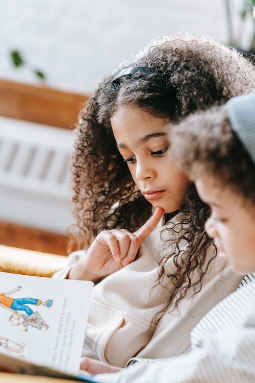Focused black kids reading book