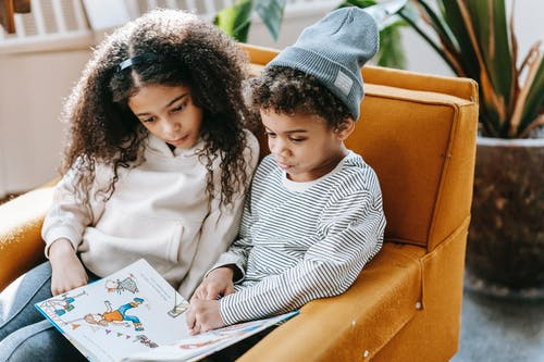 Serious black kids reading interesting book together