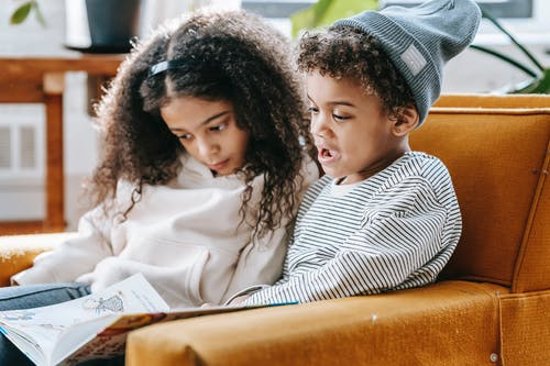 Cute smart little African American siblings with curly hair in trendy clothes sitting together in comfortable armchair and reading book