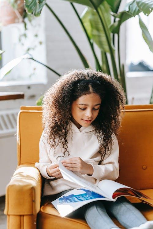 Pensive black girl reading magazine in living room in sunny day