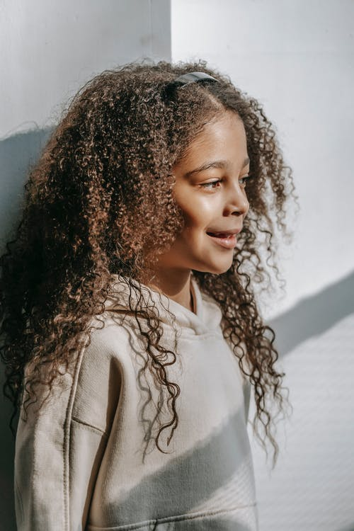 Side view of African American girl with long curly hair in trendy clothes standing near white wall and looking away in sunny day