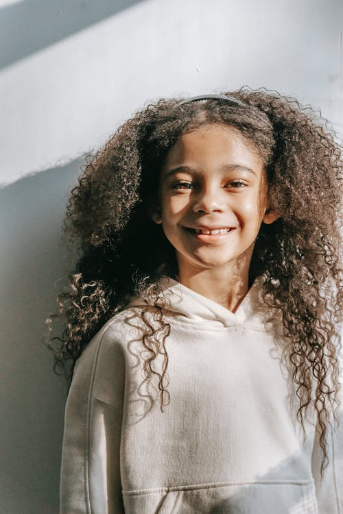 Happy black girl with long curly hair standing near white wall