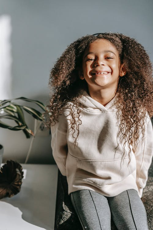 Smiling black girl with long curly hair in trendy clothes sitting on couch near table with potted plants and looking at camera