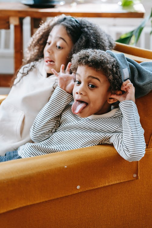 Funny black children sitting on sofa at home in daytime