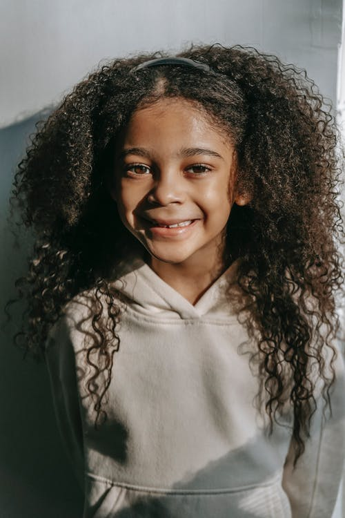 Happy African American child with long curly hair in hoodie smiling and looking at camera against white wall in sunny day