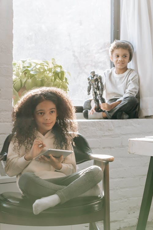 Positive African American girl with long curly hair sitting on chair and browsing tablet while spending time with brother sitting on windowsill and playing with toy at home in daytime