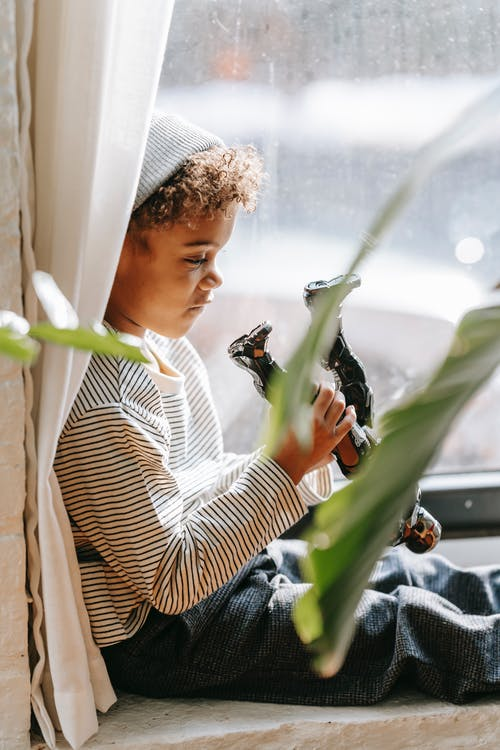 Calm black kid in casual clothes sitting on windowsill at home
