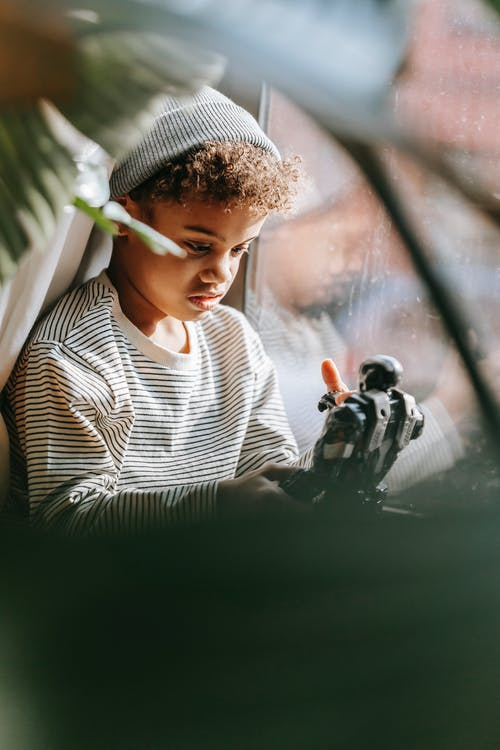Thoughtful African American boy playing with toy at home