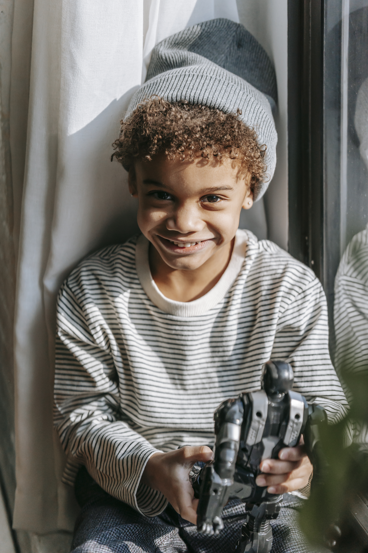 smiling black boy with robot toy near window