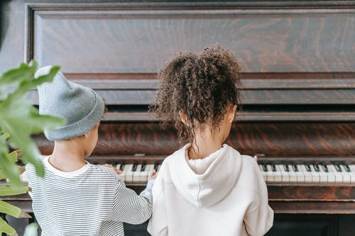 Anonymous ethnic kids playing on piano in room