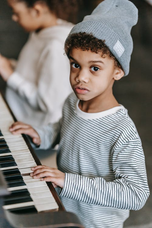 African American kids playing piano at home