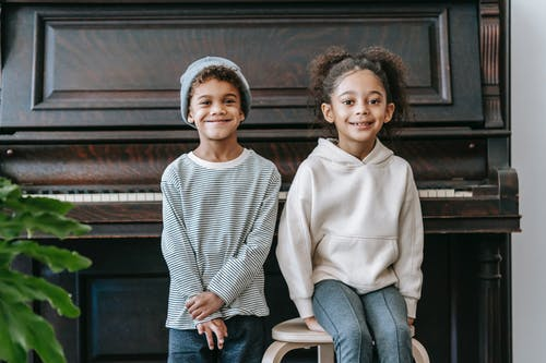 Happy African American children in casual outfits in bright room near piano and plant with green leaves looking at camera