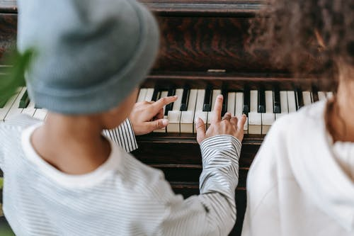 Back view of crop anonymous ethnic kids in casual clothes playing piano together in bright room