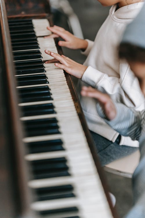 Anonymous ethnic children playing piano in room