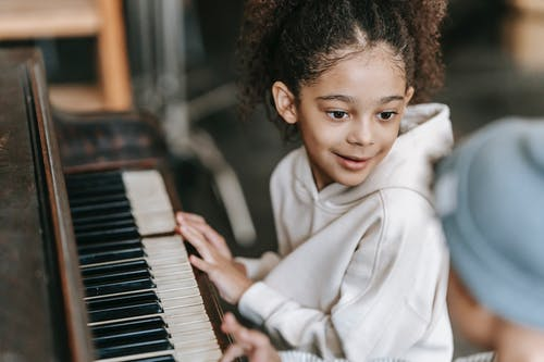 Ethnic children playing on piano in house