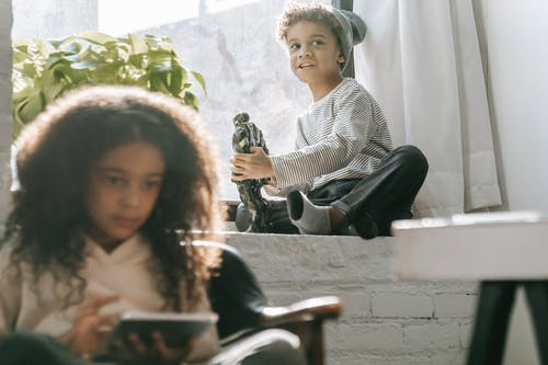 Black boy with robot toy near sister with tablet