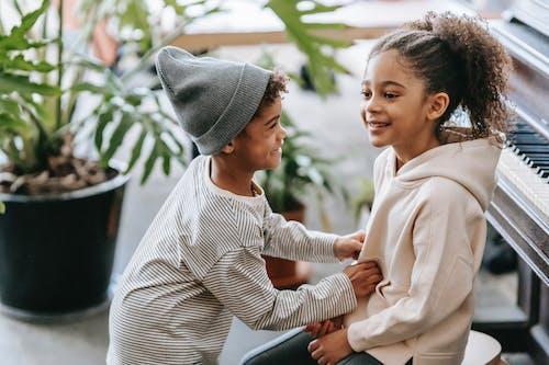 Positive black boy tickling girl near piano at home