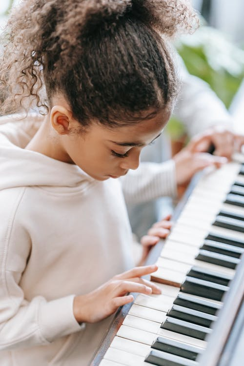 Side view of anonymous ethnic children in casual outfits playing on piano together in bright house