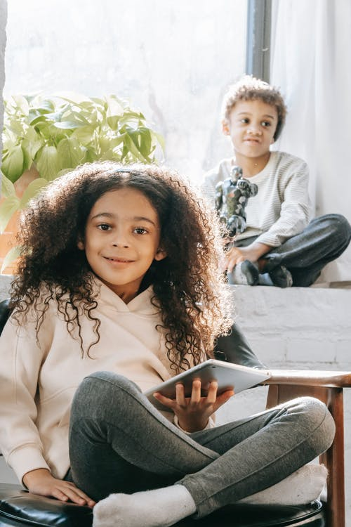 Black girl sitting in armchair using tablet near boy on windowsill playing with robot toy near window and plant with green leaves near curtains in room in sunny day