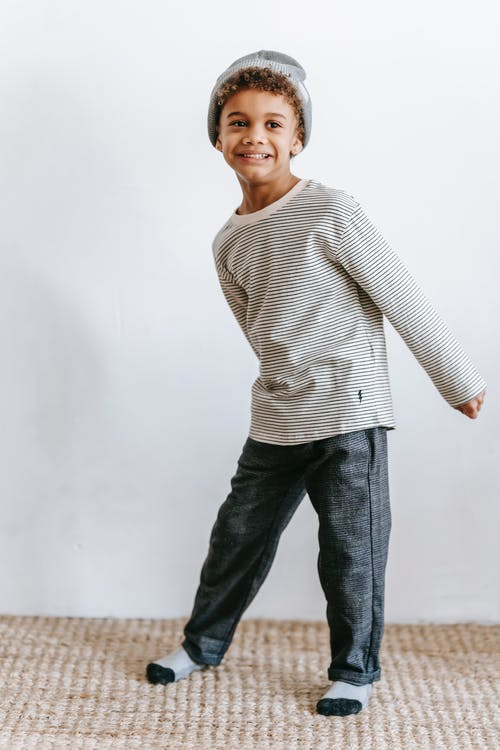 Full body of funny African American boy in hat looking away while having fun against white wall in light room