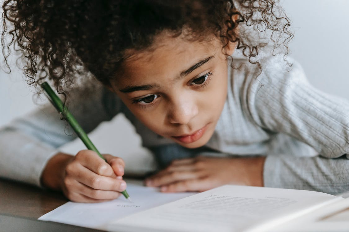 Crop concentrated African American girl with curly hair sitting at table with textbook while taking notes on sheet of paper
