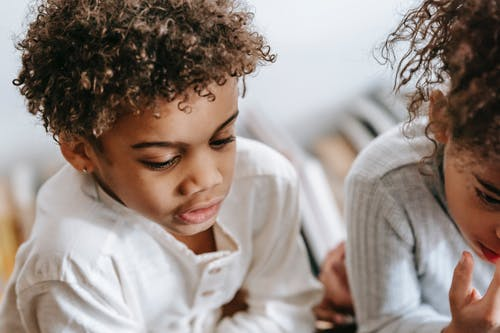 Serious African American boy with concentrated black sister sitting in light apartment with various books on blurred background at home