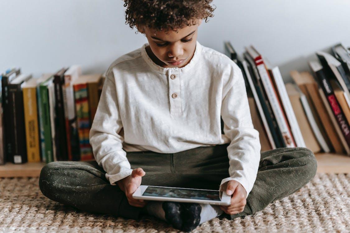 Crop black boy browsing tablet in room