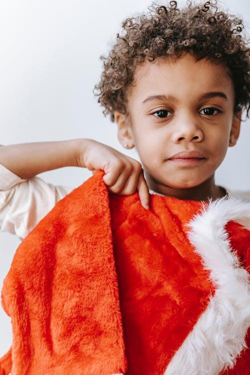 Мальчик в белой рубашке держит красный текстиль