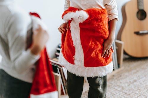 Crop children with Santa Claus costumes