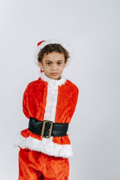 Serious black boy in Santa Claus costume